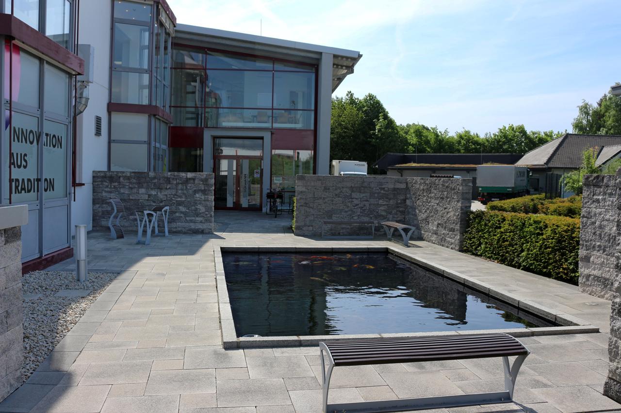 Landschaftsbau ist professionelle Arbeit: Terrasse mit Koiteich.