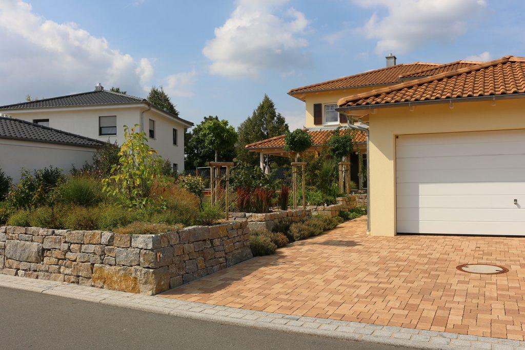 Pflasterbelag aus Beton in der Farbe rustica Latte Macchiato, dazu eine Trockenmauer aus Muschelkalkstein.